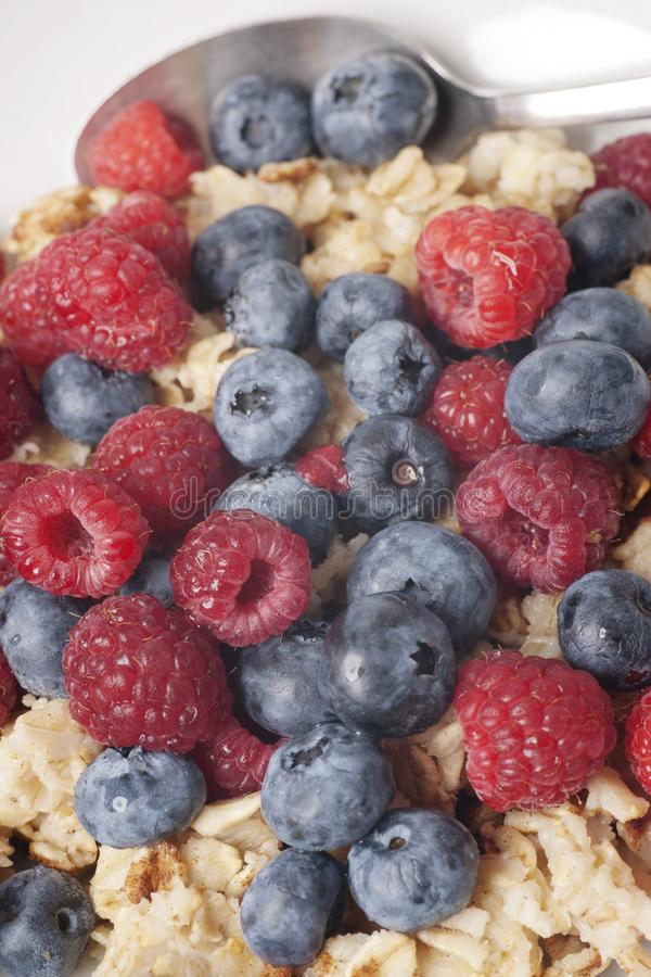 Oatmeal Breakfast  with Berries. Healthy vegetarian breakfast of oatmeal, strawberries, and blueberries in white dish with metal spoon stock photo