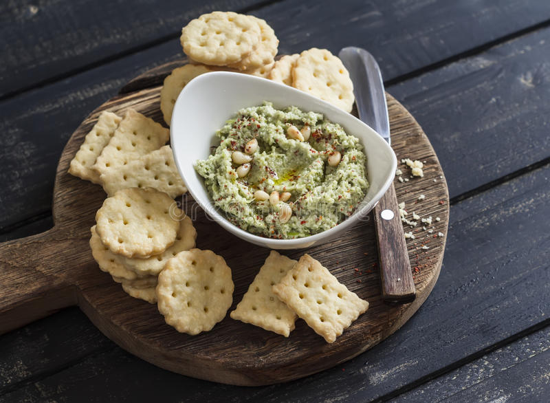 Healthy vegetarian broccoli and pine nuts hummus and homemade cheese biscuits on a wooden rustic board. royalty free stock photo