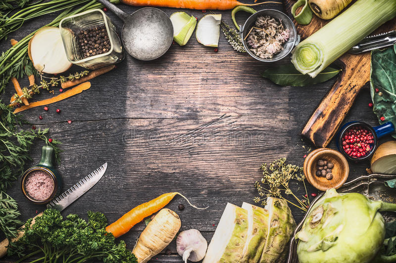 Healthy vegetarian cooking ingredients for soup or stew. Raw organic vegetables with kitchen tools on dark rustic wooden backgroun. D, top view. Country style royalty free stock image