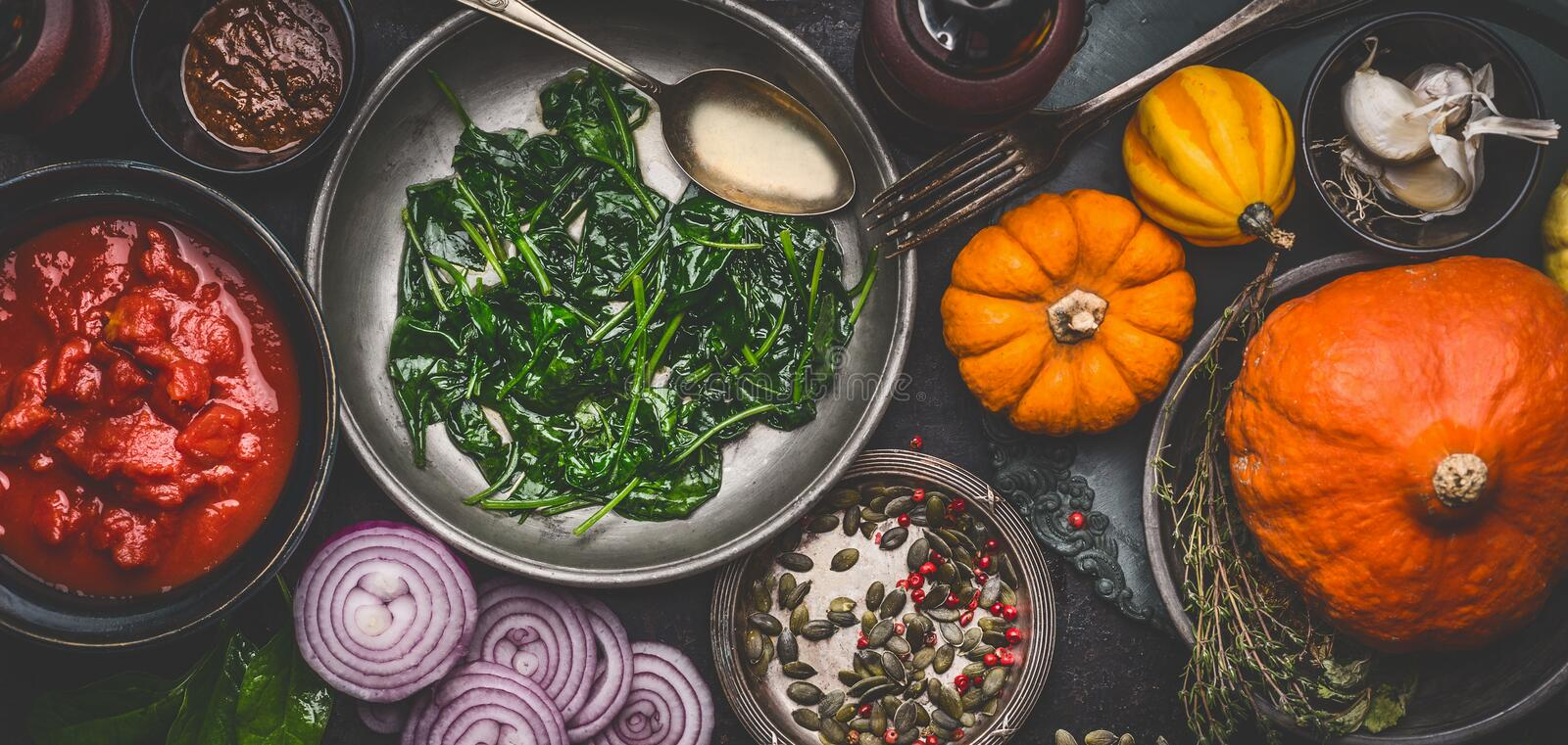 Healthy vegetarian cooking ingredients for tasty pumpkin dishes recipes in bowls : tomato sauces, spinach, sliced onion, pumpkin s. Eeds, top view, banner. Clean royalty free stock images