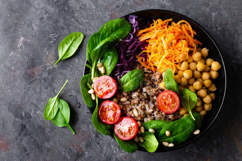 Healthy vegetarian dish with buckwheat and vegetable salad of chickpea, kale, carrot, fresh tomatoes, spinach leaves and pine nuts royalty free stock photography