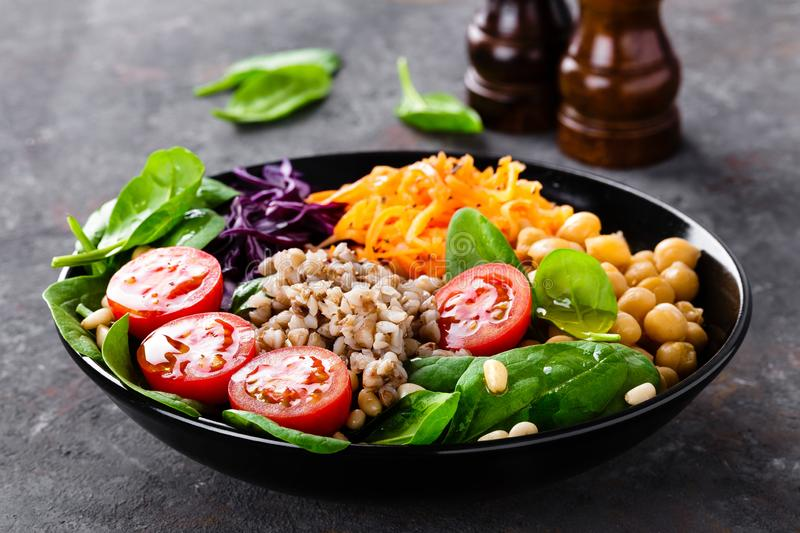 Healthy vegetarian dish with buckwheat and vegetable salad of chickpea, kale, carrot, fresh tomatoes, spinach leaves and pine nuts royalty free stock photo