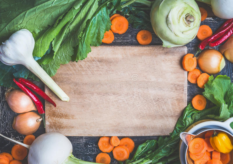 Healthy vegetarian eating and cooking with fresh organic ingredients. Various farm vegetables, Herbs,spices around rustic wooden. Gutting board background, top royalty free stock photo
