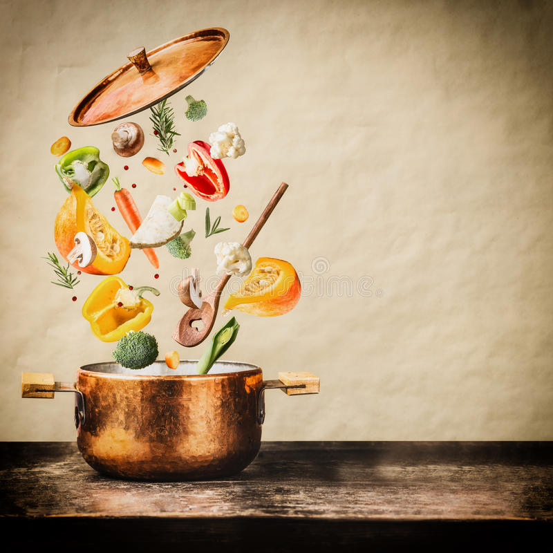 Healthy vegetarian eating and cooking with various flying chopped vegetables ingredients, cooking pot and spoon at wooden table a stock images
