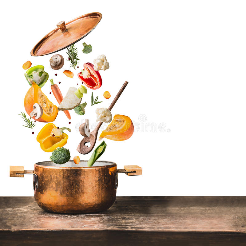 Healthy vegetarian eating and cooking with various flying chopped vegetables ingredients, cooking pot and spoon at wooden table d. Esk , isolated on white royalty free stock photos