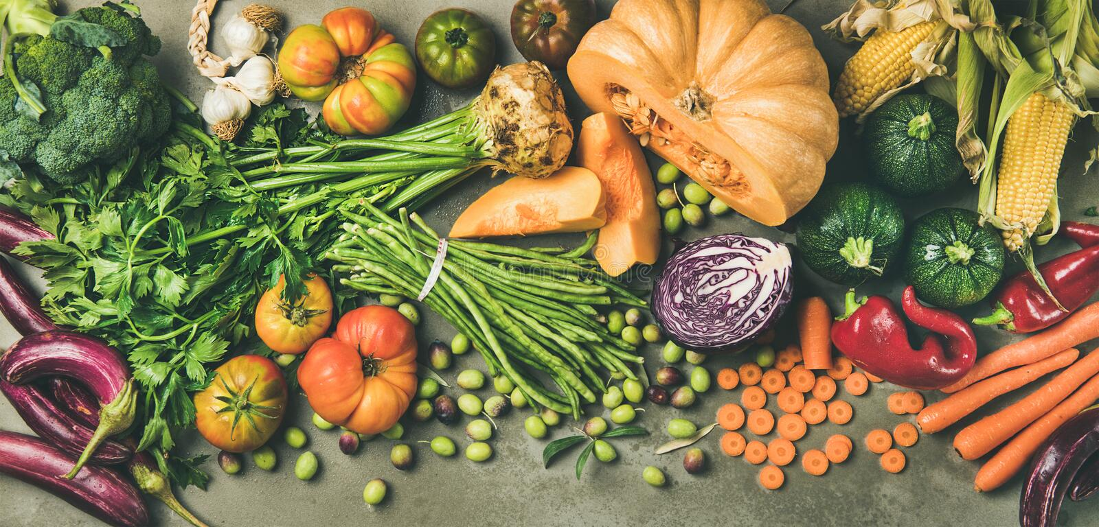Healthy vegetarian Fall food cooking ingredients over concrete table. Healthy vegetarian seasonal Fall food cooking background. Flat-lay of Autumn vegetables and royalty free stock photos