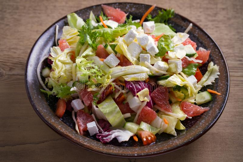 Healthy vegetarian food: citrus grapefruit, tomato, lettuce and cucumber salad with feta cheese in bowl on wooden table. Horizontal stock image
