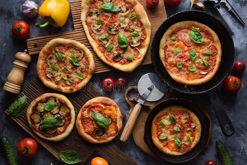Healthy vegetarian food flatlay. Homemade rustic pizzas with tomatoes, mushrooms, eggplants and basil with raw ingredients in cast royalty free stock image
