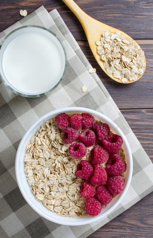 Healthy vegetarian food. Oatmeal with raspberry. Wooden spoon with cereals. Brown wooden background. Flat Lay. Vertical photo royalty free stock image
