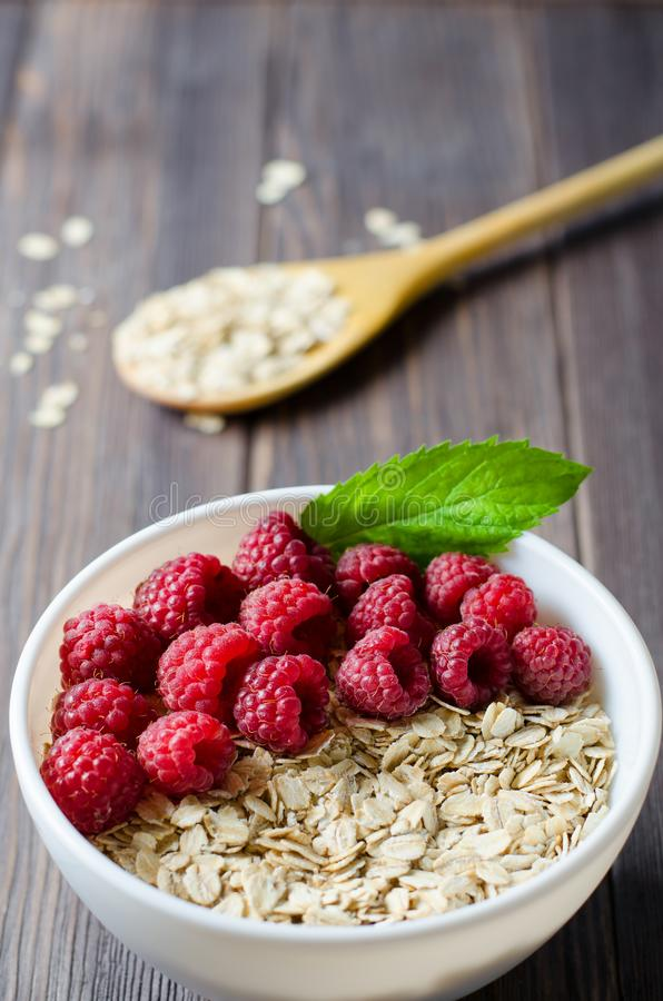 Healthy vegetarian food. Oatmeal with raspberry. Wooden spoon with cereals. Brown wooden background. Vertical photo royalty free stock photography