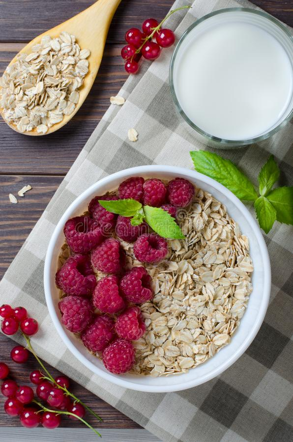 Healthy vegetarian food. Oatmeal with raspberry. Wooden spoon with cereals, milk in a glass, red currant. Brown wooden background royalty free stock photos