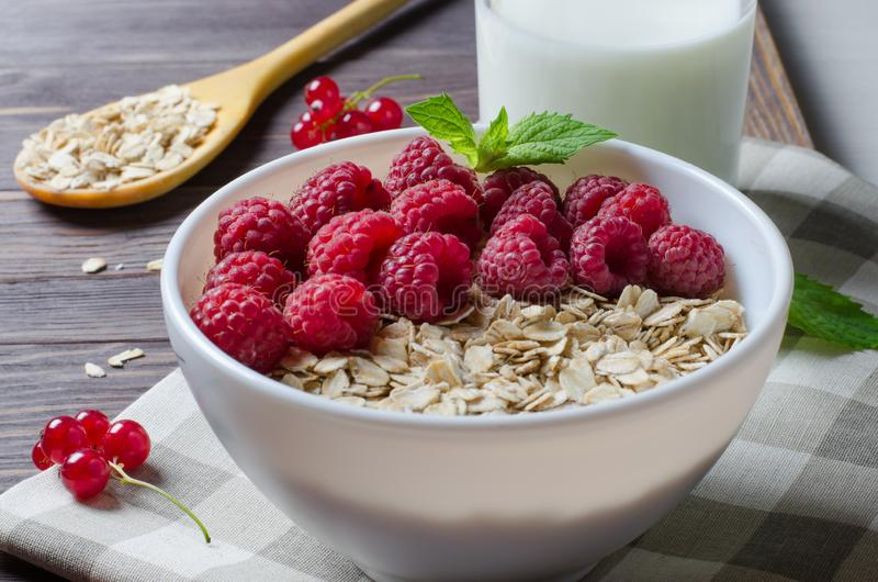 Healthy vegetarian food. Oatmeal with raspberry. Wooden spoon with cereals, milk in a glass, red currant. Brown wooden background royalty free stock image