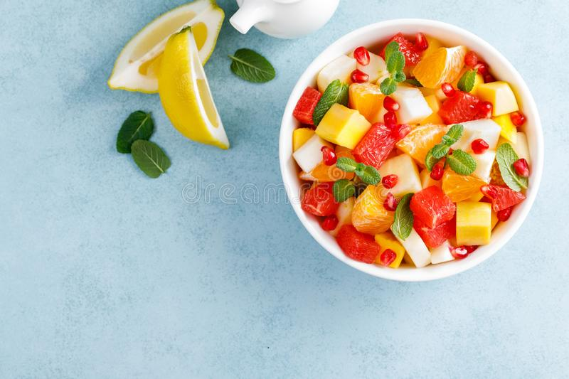 Healthy vegetarian fresh fruit salad with apple, pear, tangerine, grapefruit, mango, pomegranate and lemon juice. Top view royalty free stock images