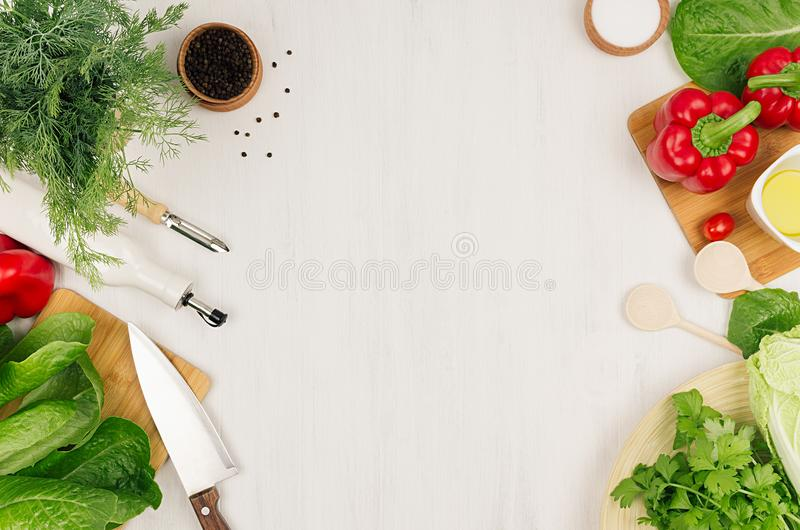 Healthy vegetarian ingredients for spring fresh green salad and kitchenware on white wood board, top view, copy space. stock images