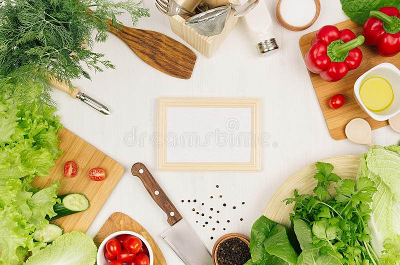 Healthy vegetarian ingredients for spring fresh green salad and kitchenware on white wood board, top view, copy space. Spring vitamin dieting food stock image