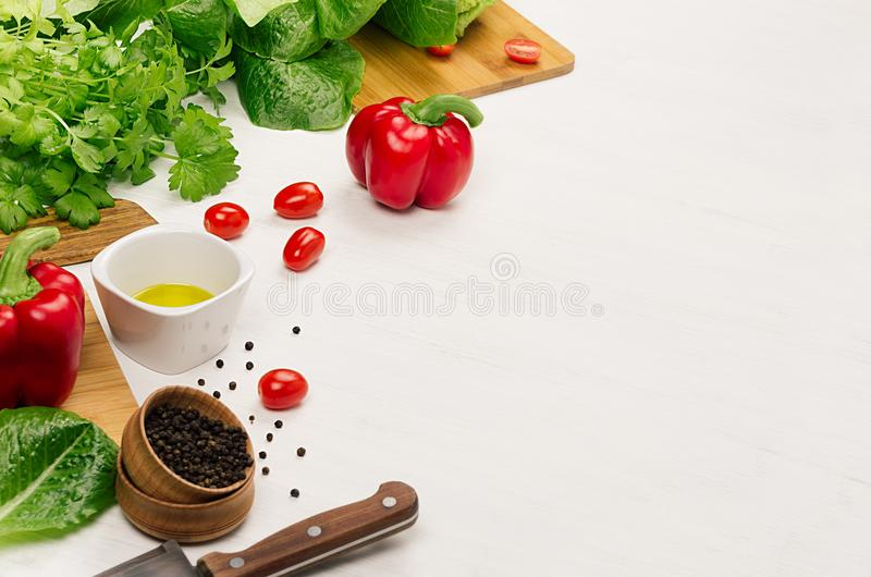 Healthy vegetarian ingredients for spring fresh green salad and kitchenware on white wood table, copy space. royalty free stock photos