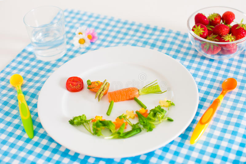 Healthy vegetarian lunch for little kids, vegetabl. Es and fruit served as animals, corn, broccoli, carrots and fresh strawberry helping children to learn eating royalty free stock photo
