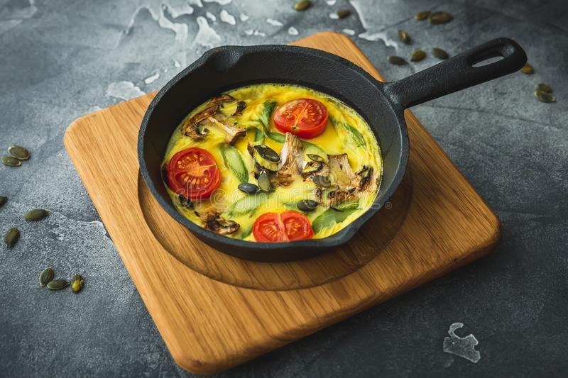 Healthy vegetarian omelet in frying pan and pumpkin seeds. Healthy vegetarian omelet in frying pan and seeds stock images