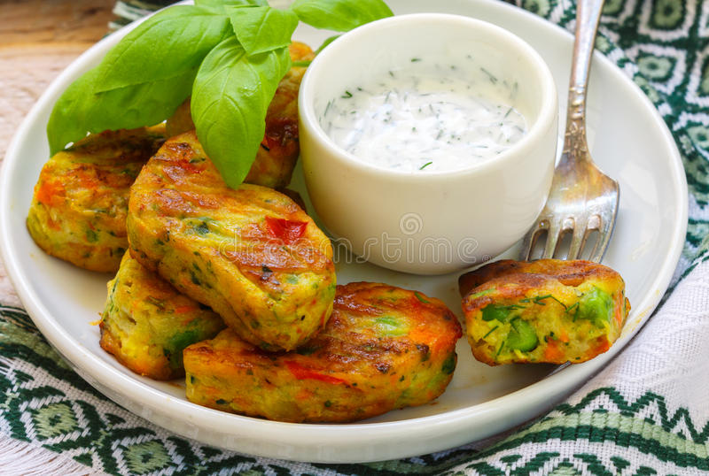 Healthy vegetarian potato patties with carrots, broccoli, bell pepper, green peas and onions with sour cream sauce with dill and. Basil. Selective focus stock image