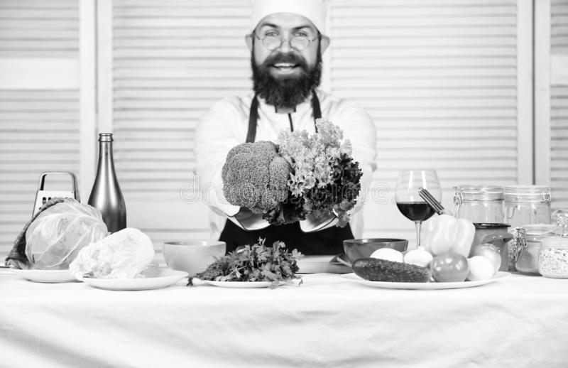 Healthy vegetarian recipe. Man cook hat and apron hold broccoli. Organic vegetables. Healthy nutrition concept. Bearded royalty free stock images