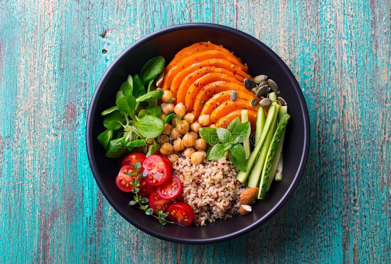 Healthy vegetarian salad. Roasted pumpkin, quinoa, tomatoes, green salad. Buddha bowl. Blue wooden background. Top view. royalty free stock photo