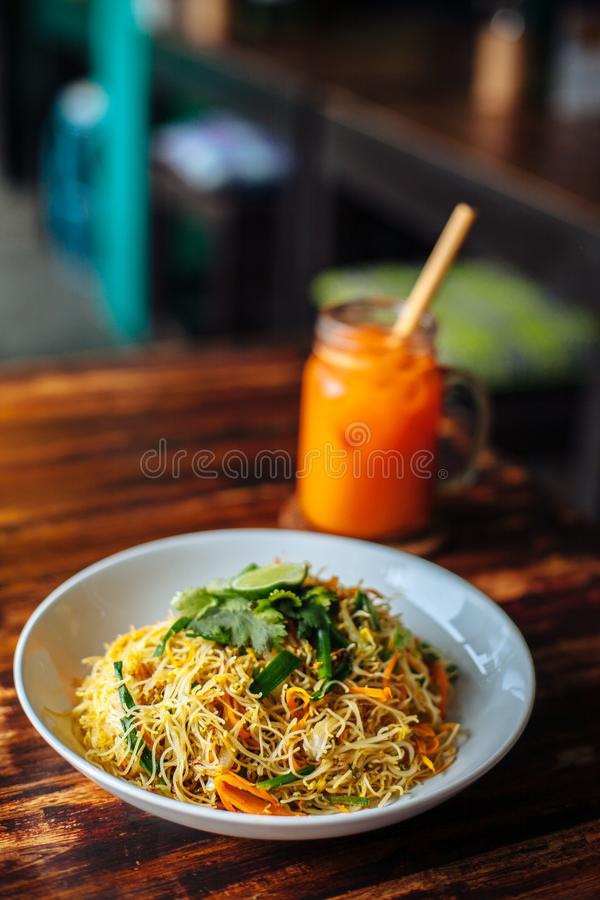 Healthy Vegetarian vegan menu Delicious Singapore style Stir fried rice noodles with carrot orange smoothies on wooden table in. Cafe stock photography