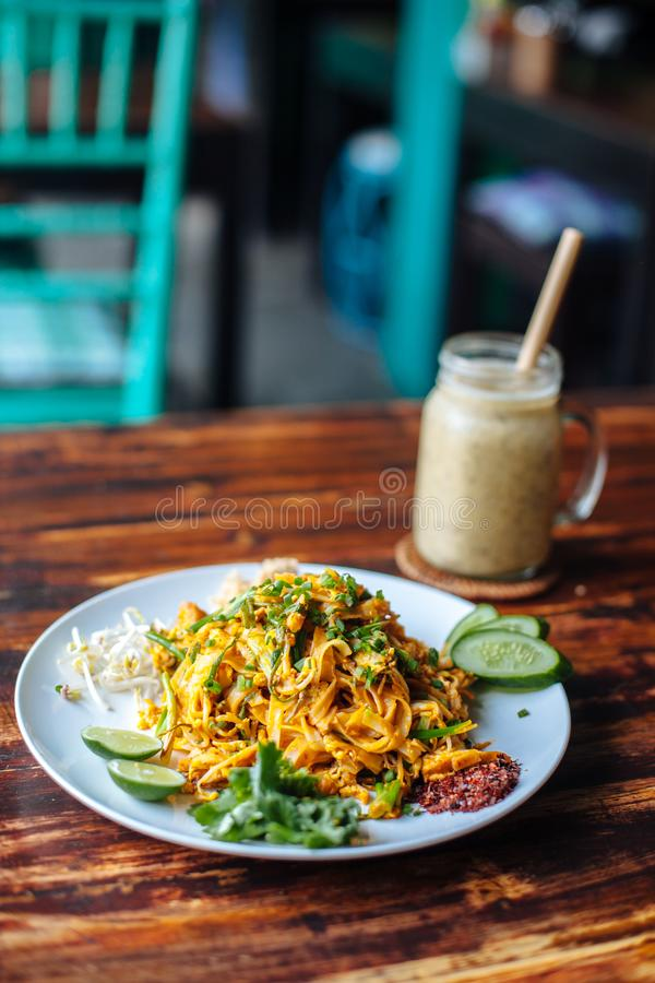 Healthy Vegetarian vegan menu Pad Thai, stir-fried rice noodles, is one of Thailand`s national main dish and banana smoothies on stock images