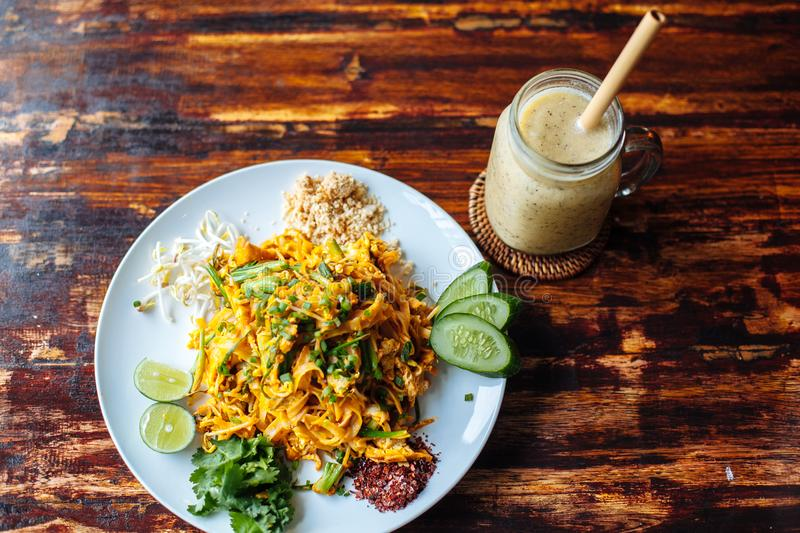 Healthy Vegetarian vegan menu Pad Thai, stir-fried rice noodles, is one of Thailand`s national main dish and banana smoothies on stock photo