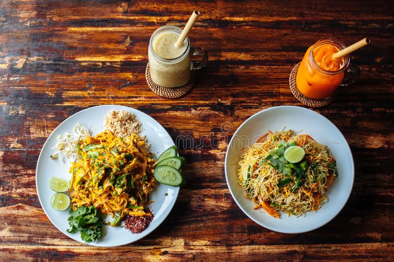 Healthy Vegetarian vegan menu Pad Thai, stir-fried rice noodles and singapore noodles and banana and carrot smoothies on stock photography
