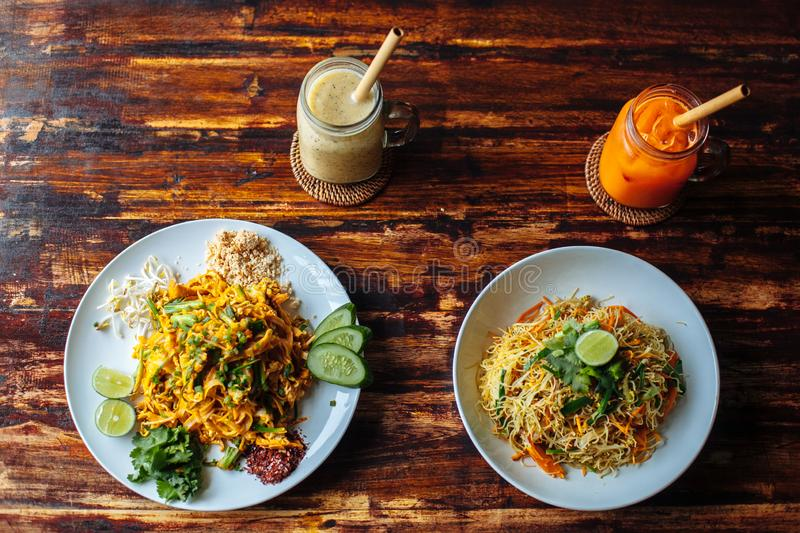 Healthy Vegetarian vegan menu Pad Thai, stir-fried rice noodles and singapore noodles and banana and carrot smoothies on wooden royalty free stock image