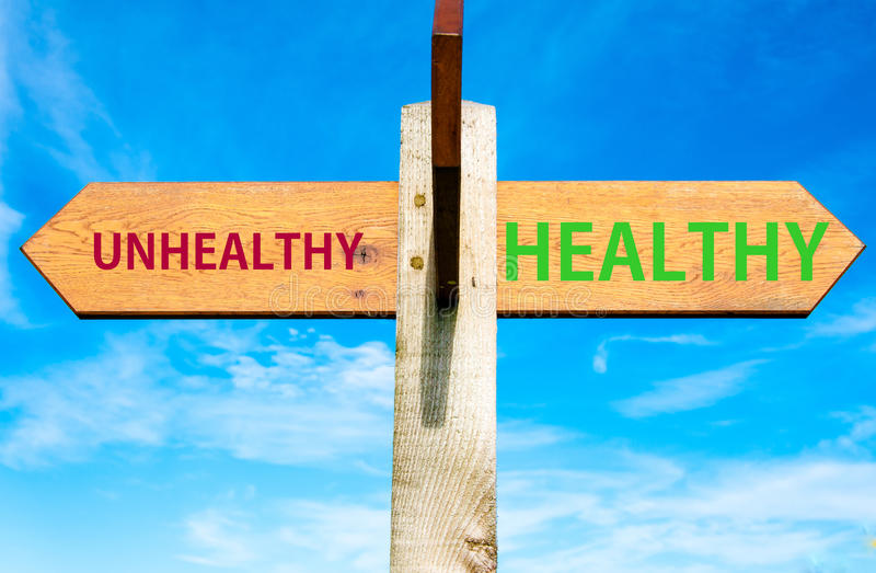 Healthy versus Unhealthy messages, Healthy Lifestyle conceptual image. Wooden signpost with two opposite arrows over clear blue sky, Healthy versus Unhealthy stock photo