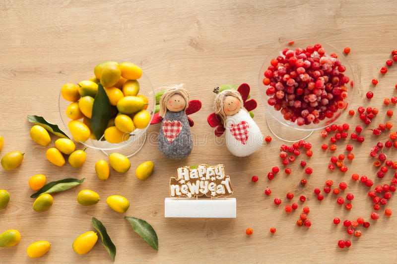 Healthy vitamin food for christmas and new year. Angels with kumquat and cranberry on wooden background royalty free stock photos