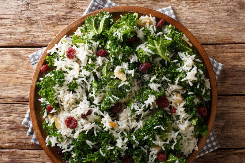 Healthy vitamin Kale with rice and cranberries close-up on a plate. horizontal top view stock image