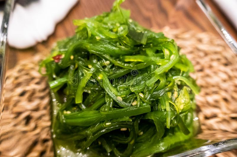 Healthy wakame seaweed salad on wooden board. Top view. stock image