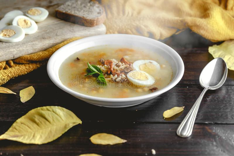 Healthy and warming winter soup with rice, carrot, chickpeas, chicken, ham and boiled egg over rustic wooden table background stock images
