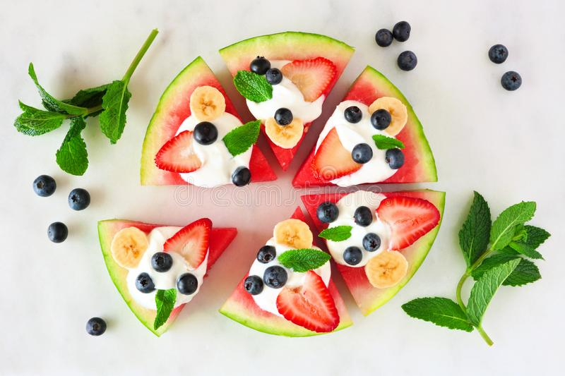 Healthy watermelon pizza with blueberries, strawberries, bananas and yogurt, above view over marble. Healthy watermelon pizza with blueberries, strawberries stock image
