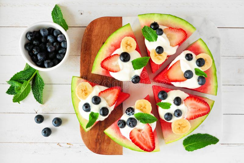 Summer watermelon pizza with blueberries, strawberries, bananas and yogurt, top view table scene against white wood royalty free stock photo