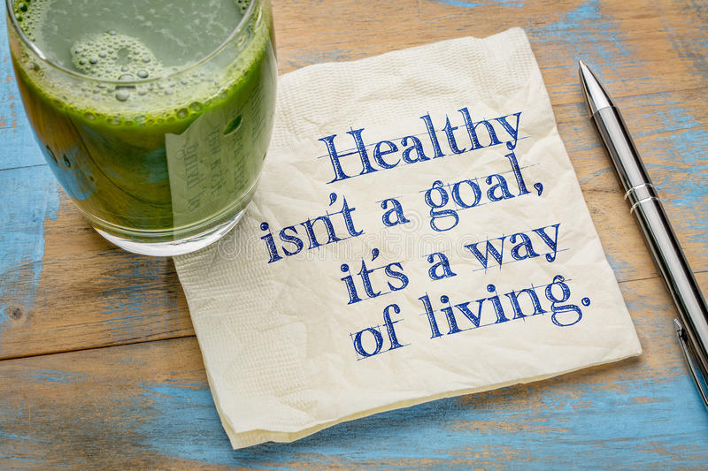 Healthy is a way of living. Healthy is not a goal, it is a way of living advice or reminder - handwriting on a napkin with a glass of fresh, green, vegetable stock images