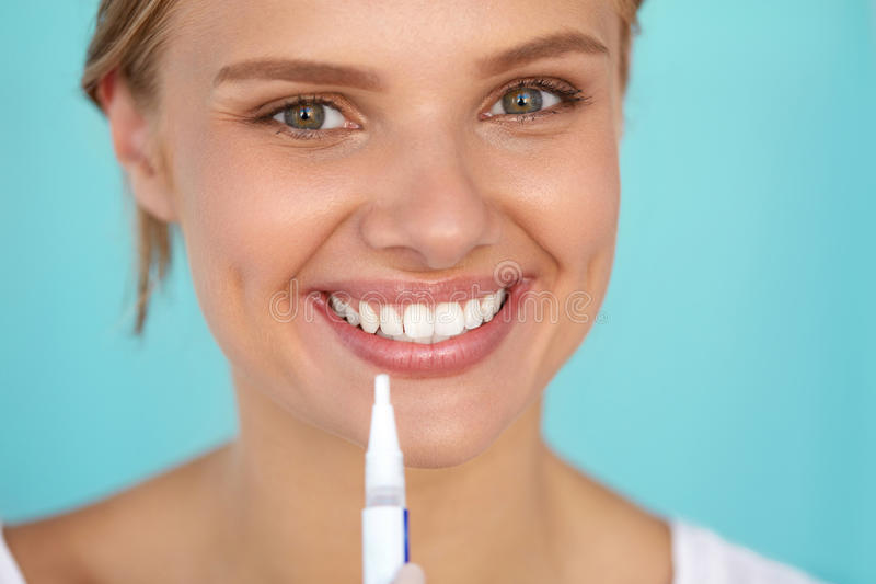 Healthy White Teeth. Beautiful Smiling Woman Using Whitening Pen. Healthy White Teeth. Closeup Portrait Of Beautiful Happy Smiling Woman With Perfect White Smile stock image