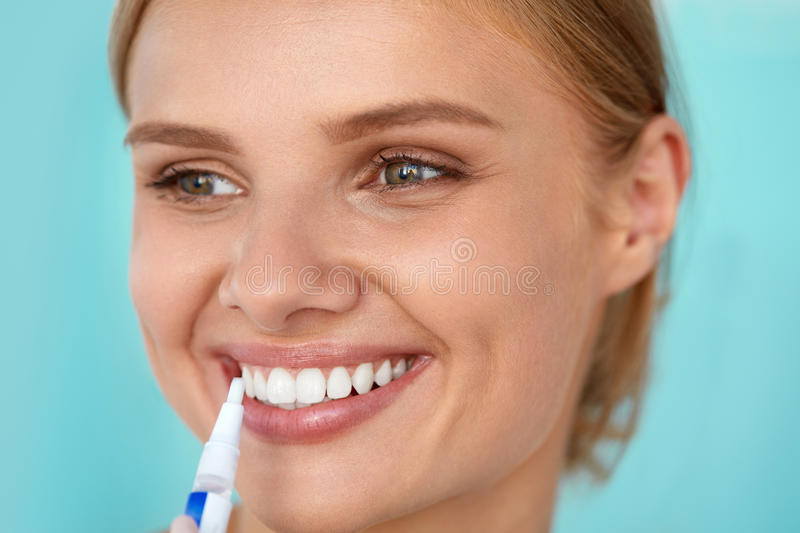 Healthy White Teeth. Beautiful Smiling Woman Using Whitening Pen. Healthy White Teeth. Closeup Portrait Of Beautiful Happy Smiling Woman With Perfect White Smile stock images