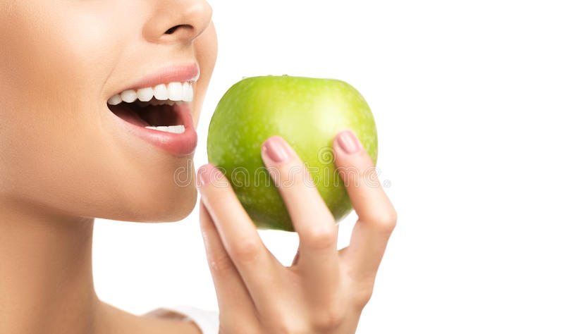 Healthy white teeth close up with an apple, isolated on white royalty free stock photography