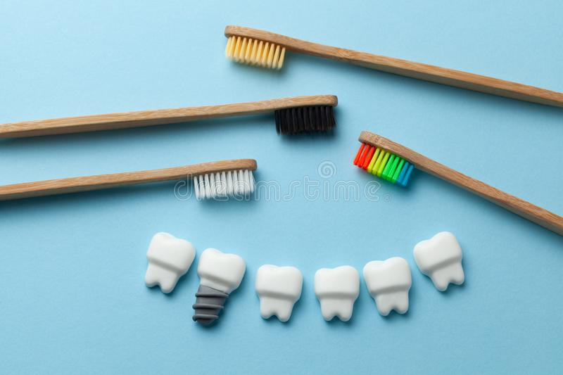Healthy white teeth and implants on blue background with toothbrush.  royalty free stock image
