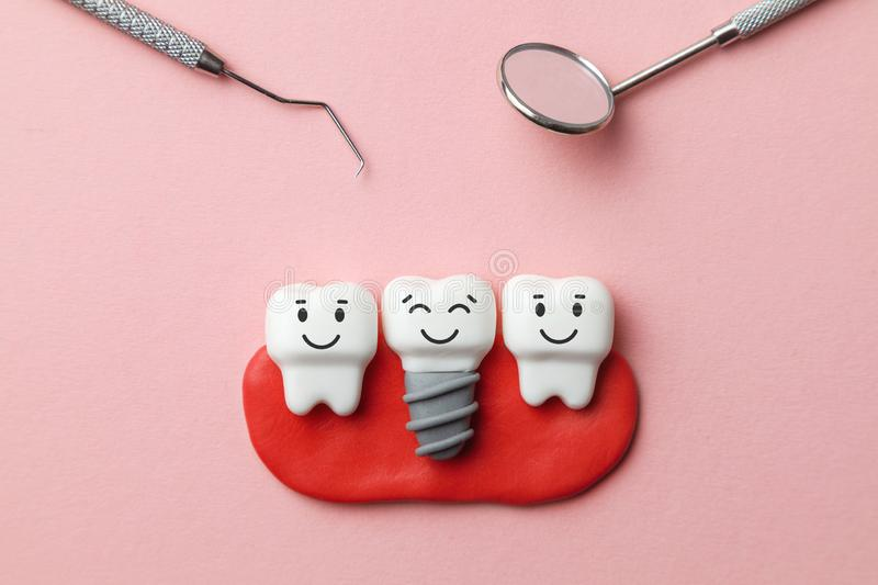 Healthy white teeth and implants are smiling on pink background and dentist tools mirror, hook. stock images