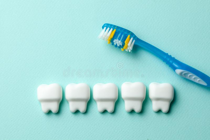 Healthy white teeth on mint green background with toothbrush.  stock image