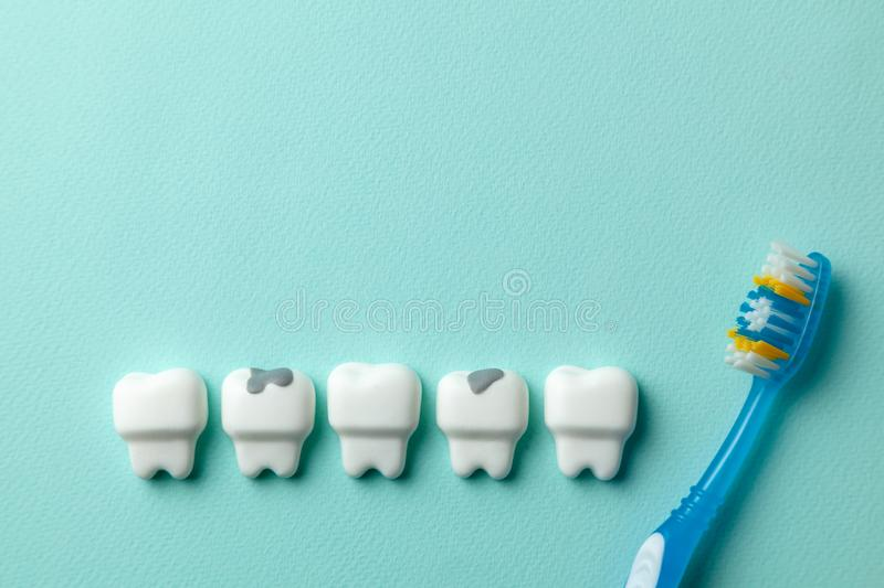 Healthy white teeth and tooth with caries on green mint background and Toothbrush. Healthy white teeth and tooth with caries on green mint background and stock photos