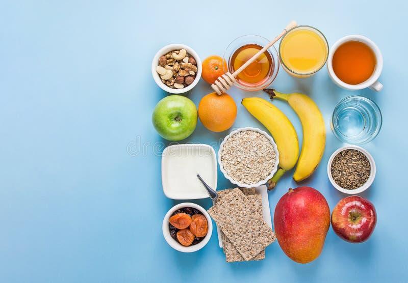 Healthy whole food fiber source breakfast with rolled oats honey fruits apples banana citrus mango orange juice water herbal tea royalty free stock photo