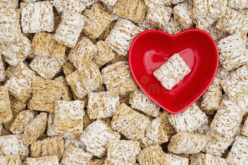 Healthy whole grain cereal background with a heart bowl. Whole grain wheat cereal with a red heart shaped bowl for a healthy cereal background stock photography
