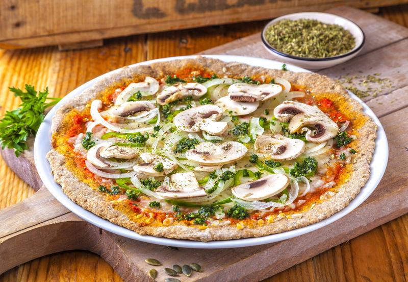 Whole wheat pizza with tomato, cheese, mushrooms, onions and pesto. stock photos