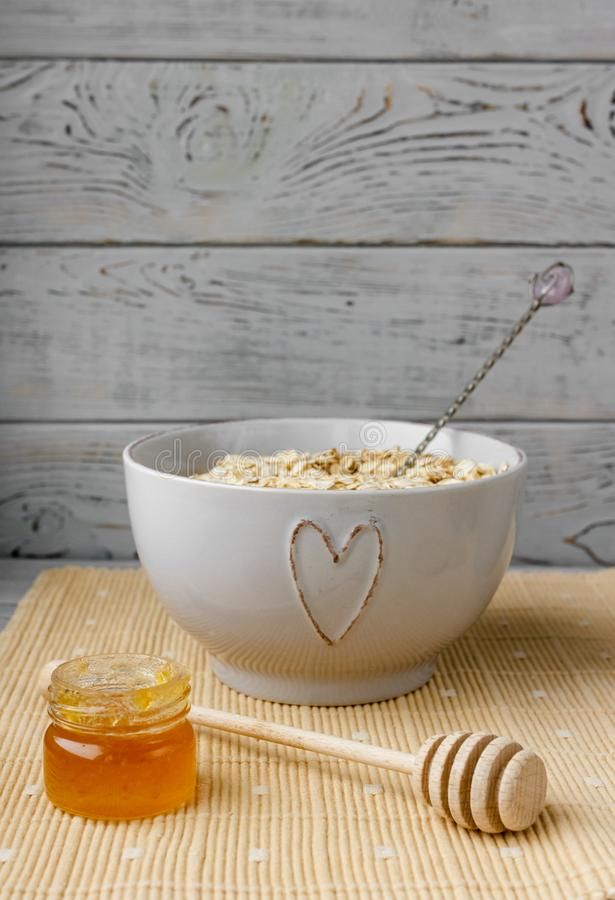 Healthy wholegrain breakfast: oatmeal, milk, biscuits, honey and vase with roses. Healthy breakfast: oatmeal cereal, cup of milk, jar of homemade jam, oatmeal stock photo