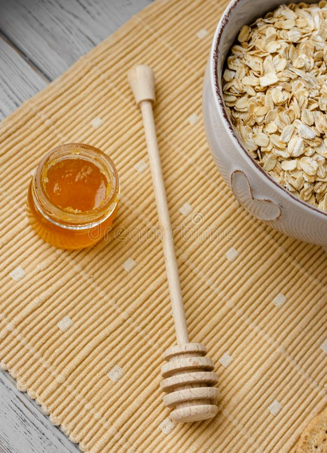 Healthy wholegrain breakfast: oatmeal, milk, biscuits, honey and vase with roses. Healthy breakfast: oatmeal cereal, cup of milk, jar of homemade jam, oatmeal stock photos